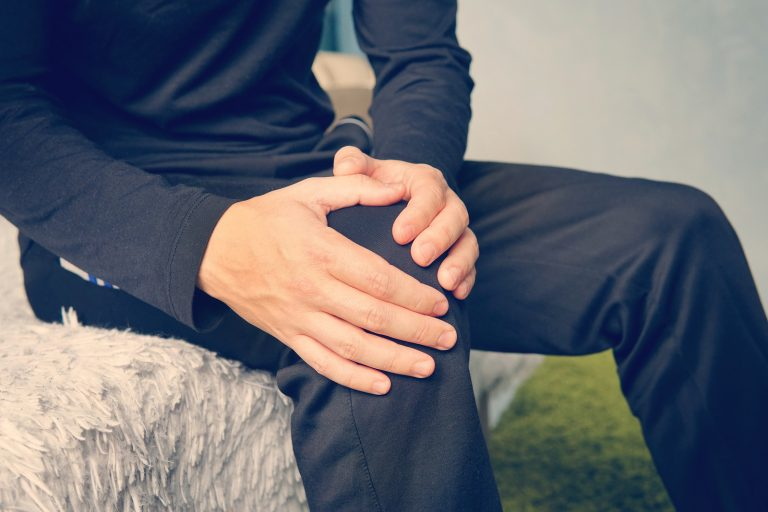 Young man suffering from leg pain at home. tendonitis inflammation of the ligaments.