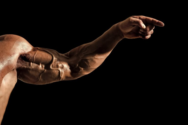 steel muscles. Hand with veins, muscles, biceps, triceps point finger on black background. Strength, power concept. Sport, fitness, bodybuilding.