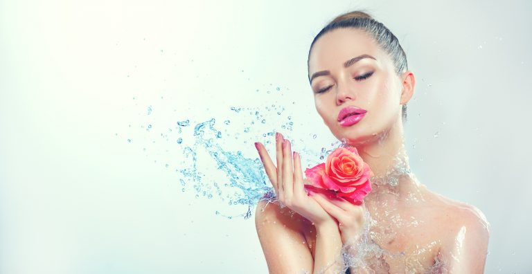 Beautiful Spa Model Woman with splashes of water and rose in her hands. Beautiful Smiling girl with splash of water with fresh skin over blue background. Skin care Cleansing and moisturizing concept