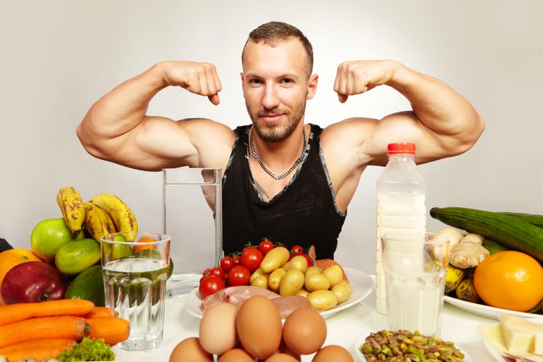 Muscle fitness man with his healthy food menu on plates