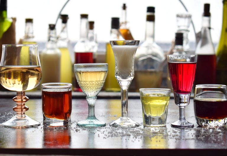 Selection of alcoholic drinks. Set of wine, brandy, liqueur, tincture, cognac, whiskey in glasses. Large variety of alcohol and spirits for making cocktails and drink. Copy space for text.