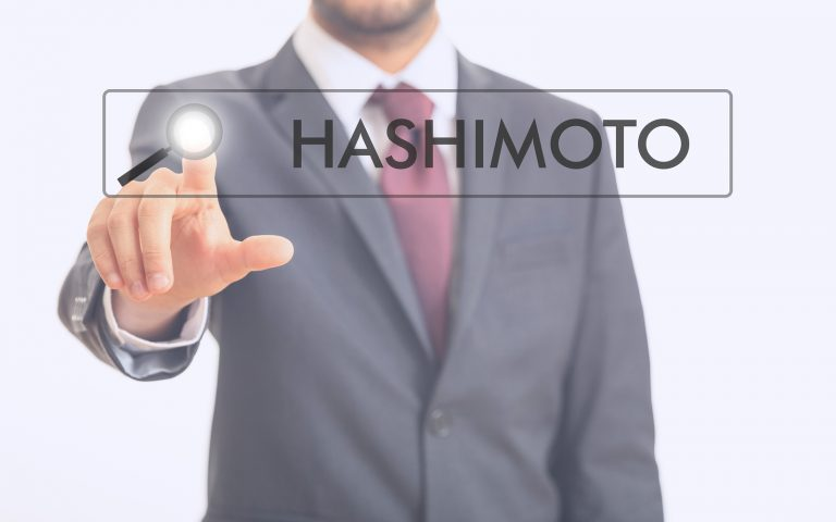 Man pointing at word Hashimoto on white background