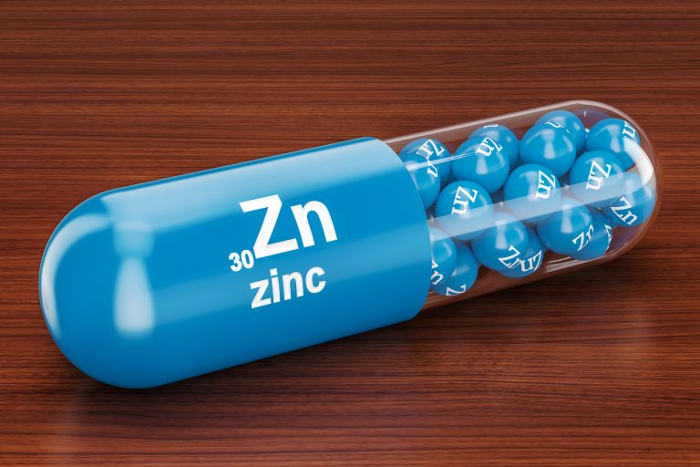 Capsule with zinc Zn element on the wooden table. 3D rendering
