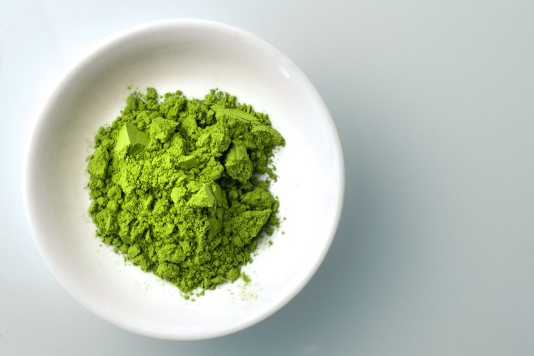 Matcha powder in white bowl. Matcha is finely ground japanese green tea leaves, this superfood has many health benefits and is packed with antioxydants, which is why it is often used in detox diets.