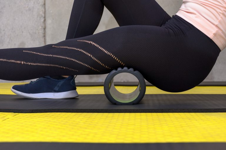 Close up view of woman exercising with foam roller at gym