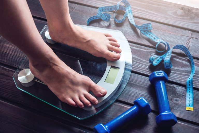 Female feet standing on electronic scales for weight control dumbbells and measuring tape on wooden background. The concept of sports training slimming and weight loss