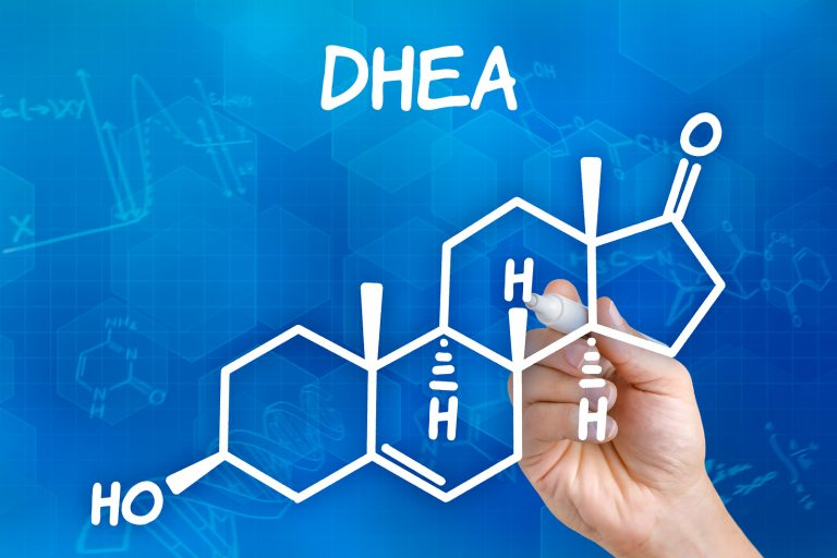 Hand with pen drawing the chemical formula of DHEA