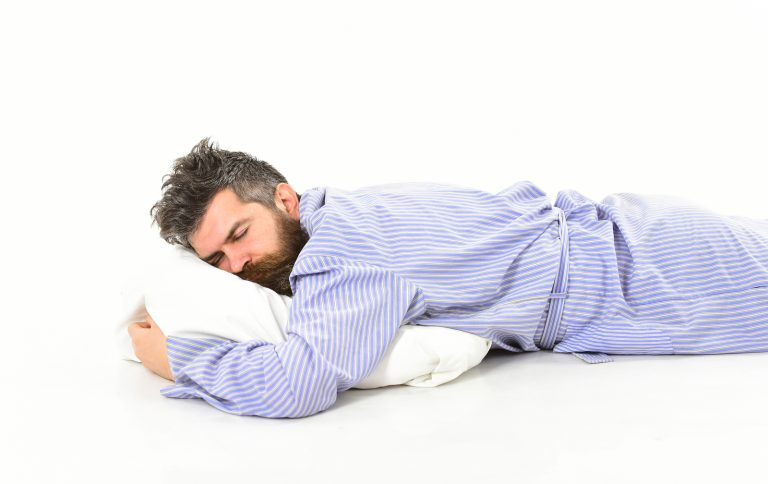 Man with sleepy face lies on pillow. Hipster with beard and mustache sleep. Man with messy hair sleep, morning, need to get up, white background. Fast asleep concept.