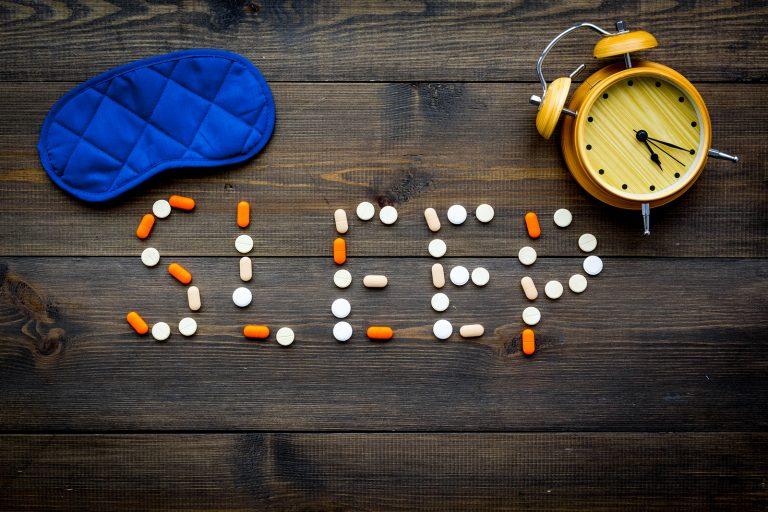 Medicine helps get asleep. Good sleep. Word sleep lined with sleeping pills near sleeping mask and alarm clock on dark wooden background top view.