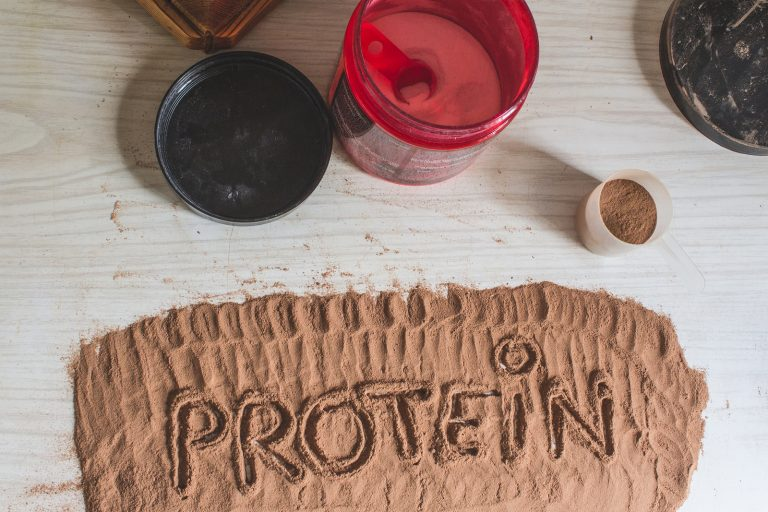 Spoonful of whey protein, with the word protein written. Sport Nutrition.