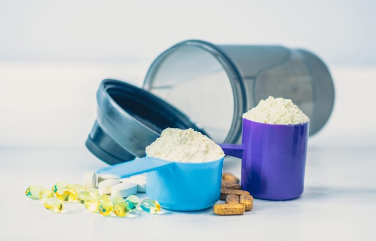 Sport food supplements. Sport Pills, vitamins and protein powder on the white table