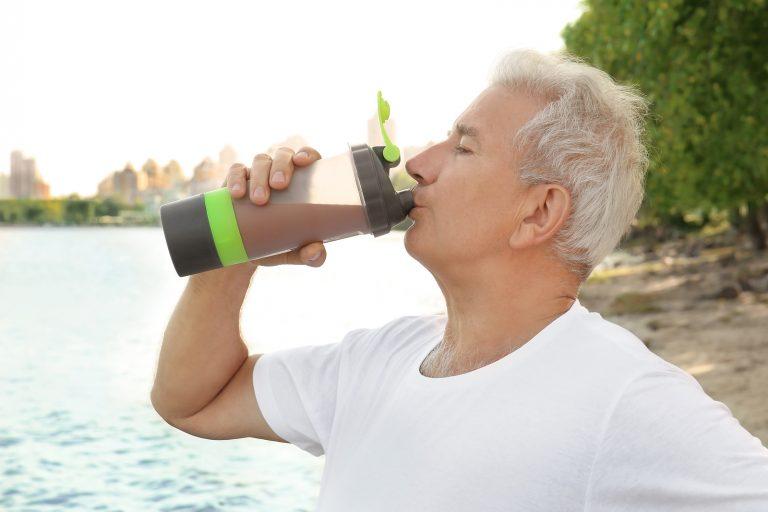 Sporty senior man drinking protein shake, outdoors