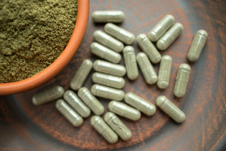 Supplement kratom green capsules and powder on brown plate. Herbal product alt-medicine kratom is  opioid. Home alternative pain remedy, opioid addiction, dangerous painkiller, overdose. Close up. Selective focus