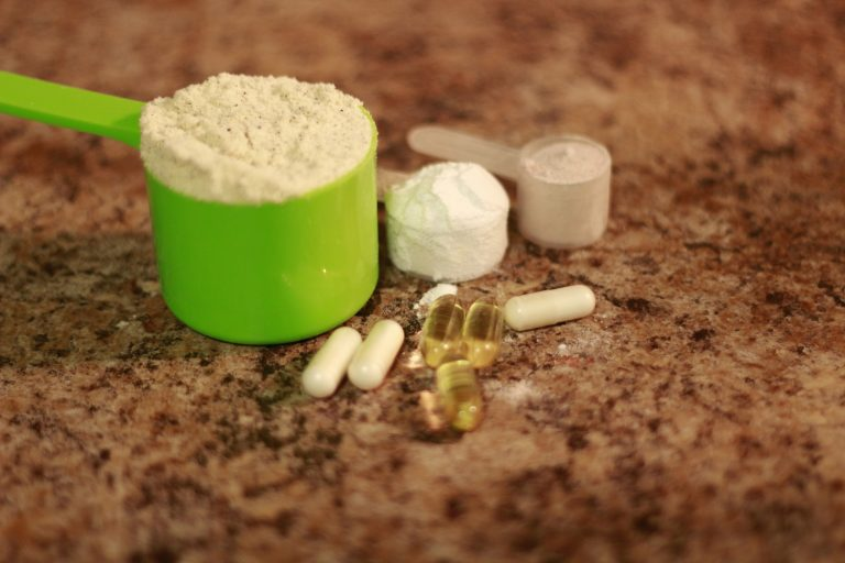 Whey protein powder in scoop with vitamins. athletes require multiple supplements to remain healthy. supplements also help everyday people reach their goals faster. Some supplements are considered useless such as glutamine however the controversy around s