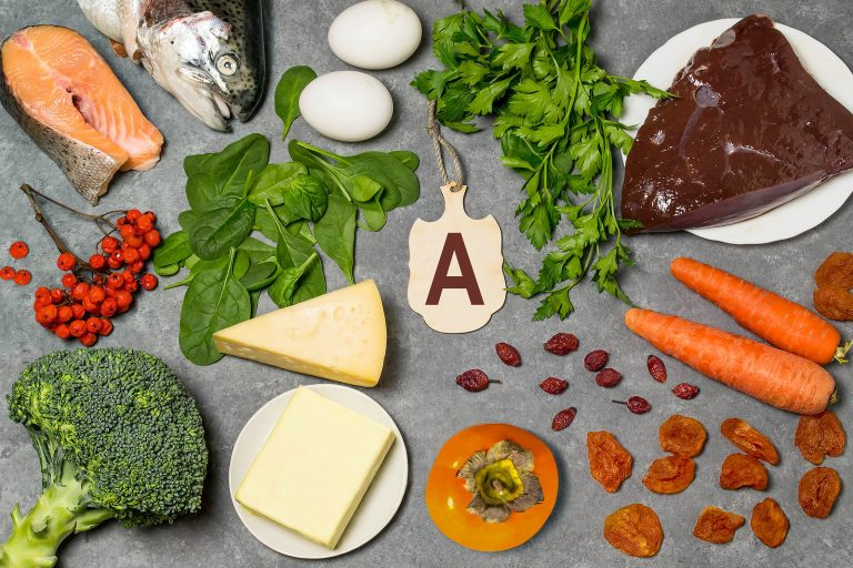 Food is source of vitamin A. Various natural food rich in vitamins. Useful food for health and balanced diet. Prevention of avitaminosis. Small cutting board with name of vitamin A. Top view