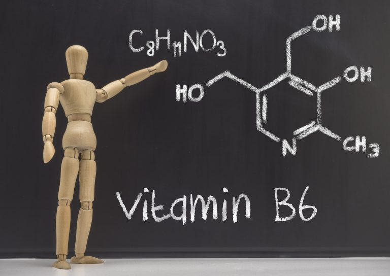 Doll articulated teaches in a blackboard the chemical composition of the vitamin B6, conceptual image