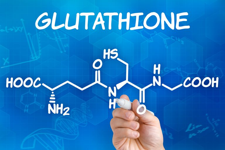 Hand with pen drawing the chemical formula of Glutathione