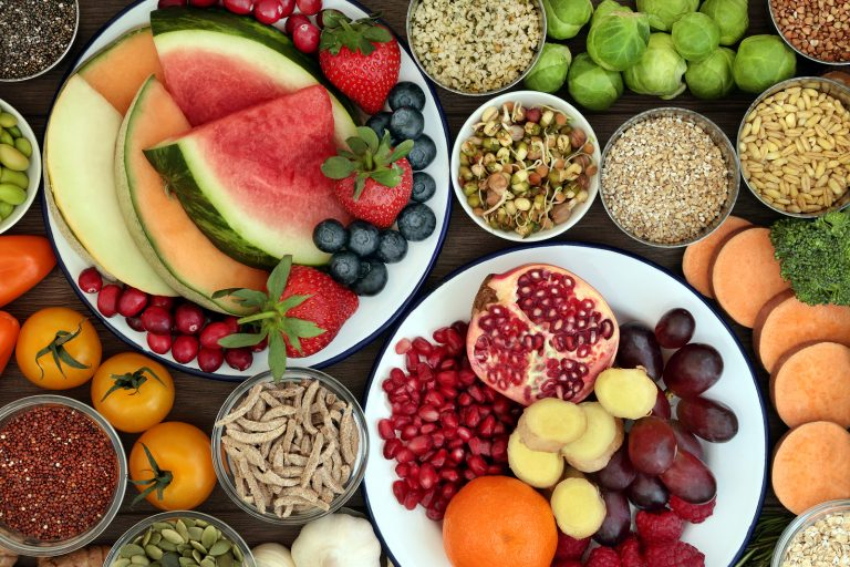 Health food concept with fresh fruit, vegetables, seeds, pulses, grains and cereals with foods high in vitamins, minerals, anthocyanins, antioxidants and fiber, top view.