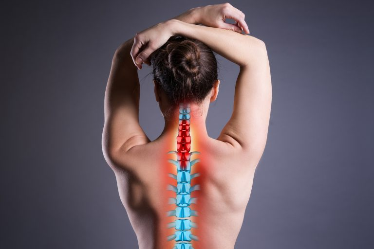 Pain in the spine, woman with backache on gray background, back injury, photo with highlighted skeleton