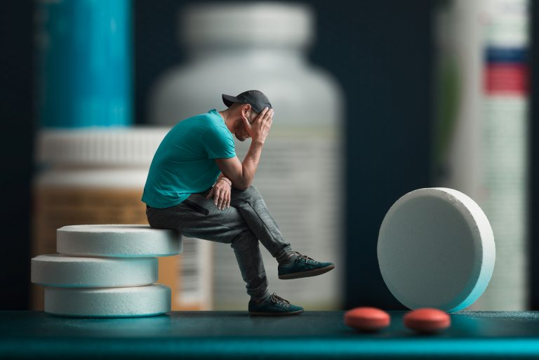 The man sitting on the pills. He's depressed. Flacons of medicines in the background. Collage.