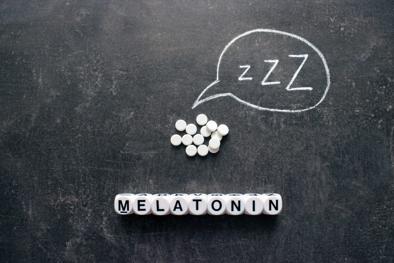 White pills in Z shape and text. Sleeping pills, hypnotic drugs, sedative, melatonin on dark night background