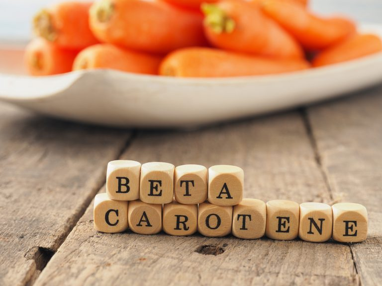 Wooden dices with the words beta carotene and fresh carrots in the back, healthy eating concept