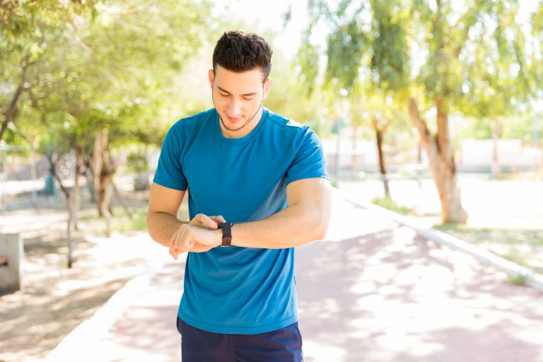 Athletic young man checking step counts on smart watch in park during sunny day