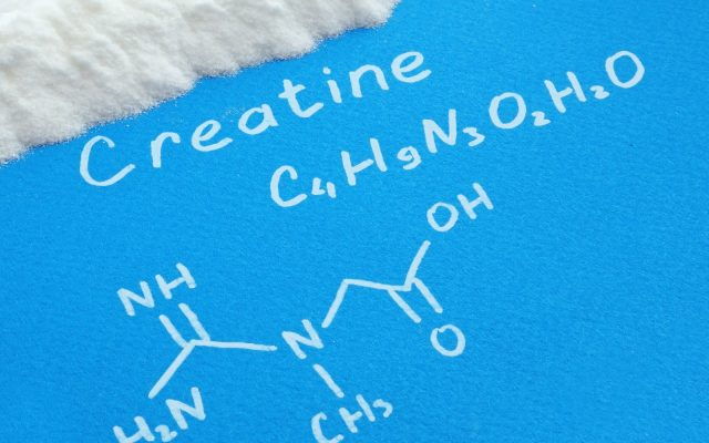 Creatine powder with  chemical formula of creatine on a blue paper
