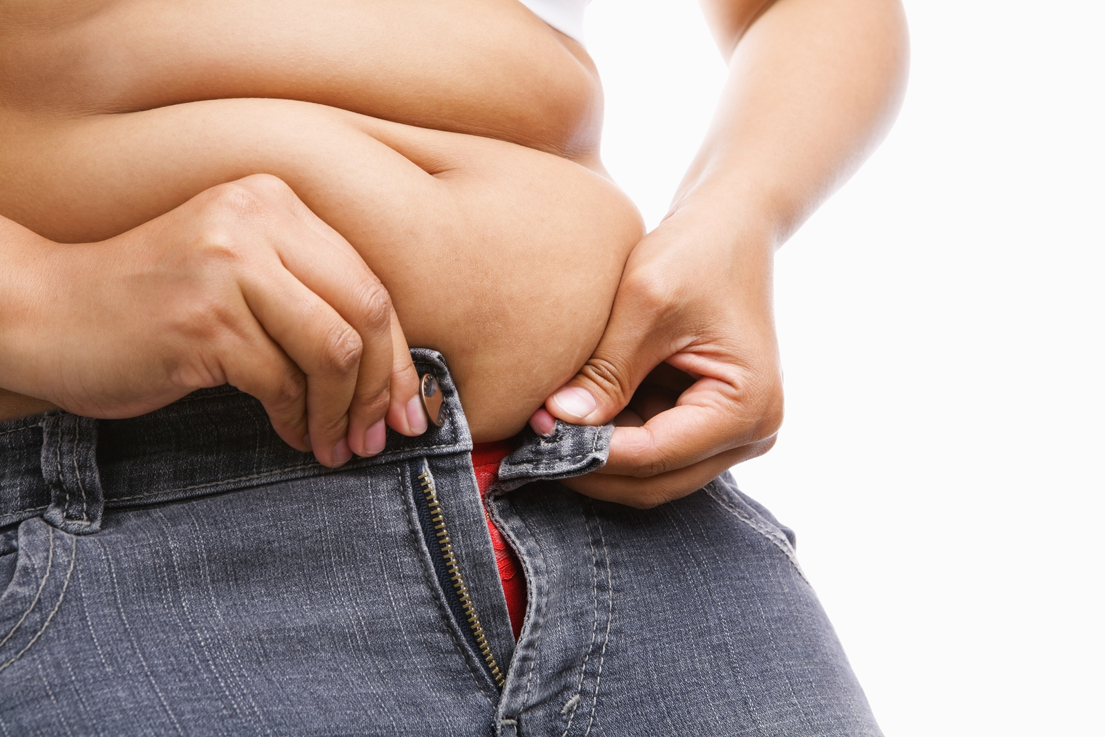 Woman trying hand to zipper her jeans a concept for obesity issue