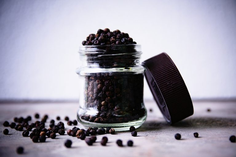 Fresh spicy peppercorns in a glass jar on a wooden background.
