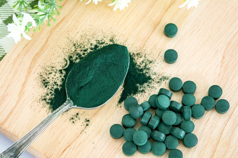 Close up  a spirulina powder  and spirulina pills in spoon , healthy superfood diet and detox nutrition concept