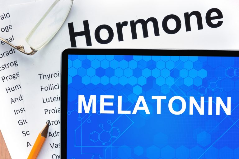 Papers with hormones list and tablet  with words  melatonin. Medical concept.