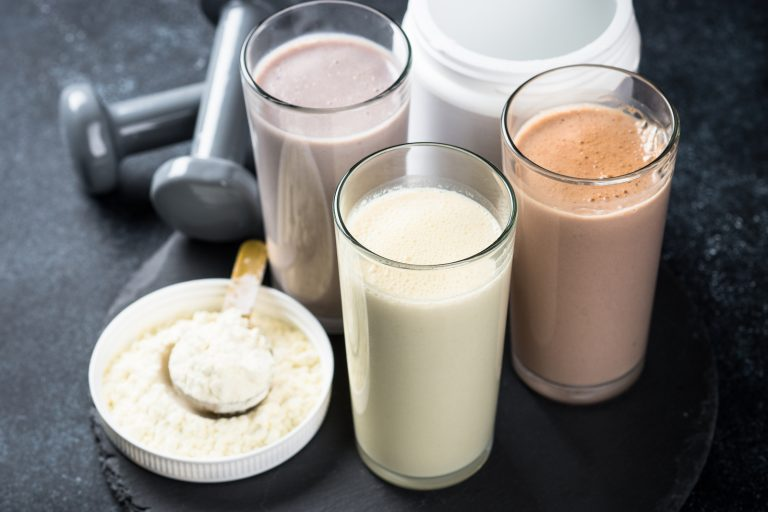 Fitness concept, Sports nutrition. Protein cocktails, protein powder and dumbbell. Vanilla, berry and chocolate protein shakes.