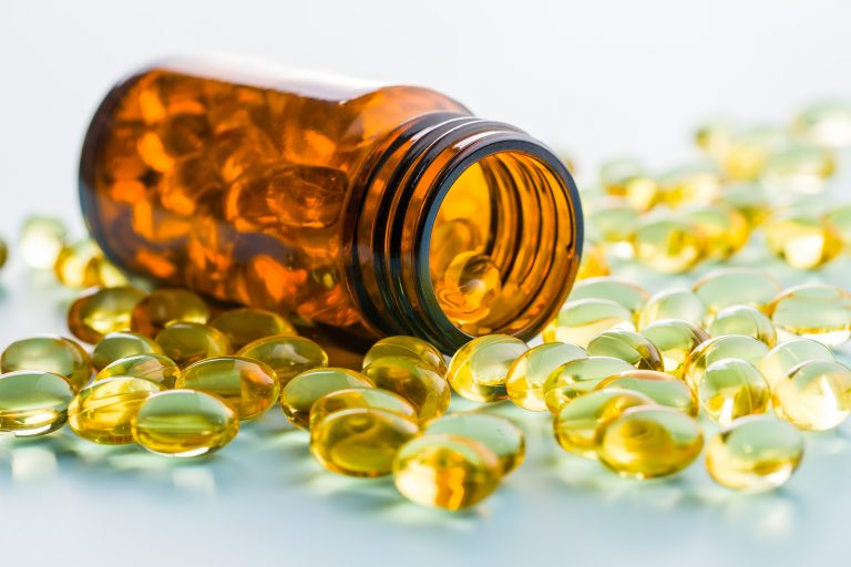 Omega 3 gel capsules. Fish oil pills. Healthy omega-3 in glass bottle.