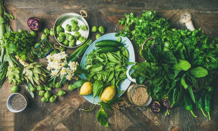 Spring healthy vegan food cooking ingredients. Flat-lay of vegetables, fruit, seeds, sprouts, flowers, greens over wooden background, top view. Diet, clean eating food concept