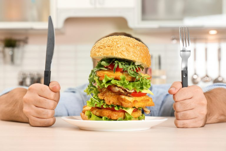 Young hungry man with cutlery eating huge burger at table
